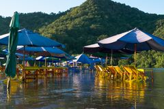 The water from the Juluapan lagoon flooded the restaurant area. In the Juluapan lagoon in Manzanillo Colima the tables, chairs and umbrellas are in the water royalty free stock photography