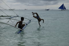 Boys Water jump in the sea near boracay. Two boys jump from ship`s rail in the sea near Puket phillipens. Vast sea water with  several sailings. grey cloud Stock Photos