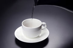 Water from the kettle is poured into a Cup for coffee Royalty Free Stock Image