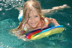 Water Kick Board. Little toddler girl uses kick board in pool to swim around Stock Images