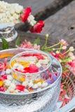 Water in kom met parfum en bloemen wordt gemengd die Stock Foto's