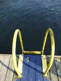 Water ladder. Yellow ladder leading in a lake Stock Photo
