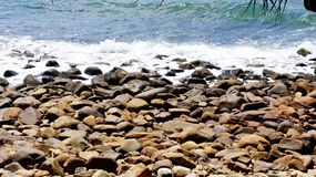 Water lapping pebble beach. Water lapping on a rocky breach Stock Image