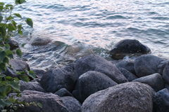 Water lapping at rocks on summer lake Stock Photos
