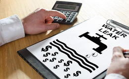 Water leak concept on a clipboard. Water leak concept with hand using a calculator Stock Image