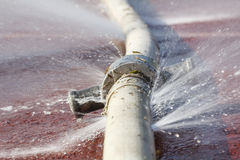 Water leaking from hole in a hose Stock Photography