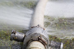Water leaking from hole in a hose. Wasting water - water leaking from hole in a hose Stock Photo