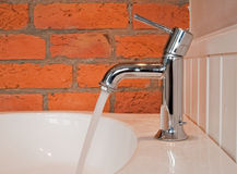 Water leaking from the tap with the old brick wall Royalty Free Stock Photo