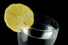 Water with lemon. In glass on the black background royalty free stock photo