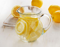 Water with lemon and ice in a glass jug. Stock Photo
