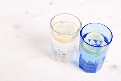 Water with lemon and mint in blue glass on the table top view Stock Images