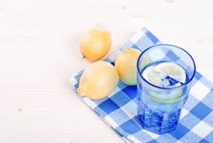 Water with lemon and mint in blue glass on the table top view Royalty Free Stock Photo