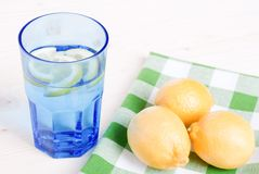 Water with lemon and mint in blue glass on the table top view Royalty Free Stock Image