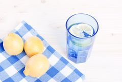 Water with lemon and mint in blue glass on the table top view Stock Photo