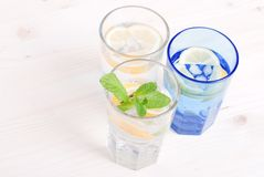Water with lemon and mint in blue glass on the table top view Stock Photos
