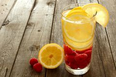 Water with lemon and raspberries against wood Stock Photo