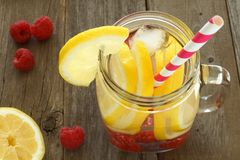 Water with lemon and raspberries in mason jar with straw Stock Photo