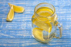 Water with a lemon on a wooden background Stock Image
