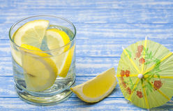 Water with a lemon on a wooden background Stock Photos