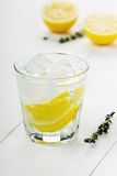 Water with lemons and ice cube. On a white board Royalty Free Stock Image