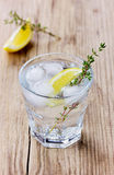 Water with lemons on a rustic wooden table Stock Photo