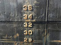 Water level depth gauge number markings on an old black ship hull fragment stock images