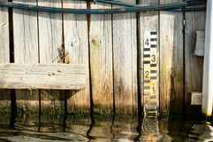 Water level marker. With numbers. Here attached to old wooden bridge stock image