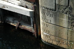 Water level markings on a dock. Water and sea level markings in Roman numerial script on the side of a dock in Liverpool, England Royalty Free Stock Image