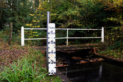 Water level measure. Picturesque English countryside with trees in the autumn, a bridge and a stream with a water level meter. With space for text Stock Photos