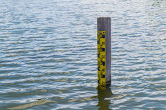 Water level pole. Water level measuring instrument is in middle of the pond royalty free stock photo