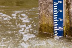 Water level pole. On a concrete wall in river stock photography