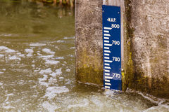 Water level pole. Water level meter on a concrete wall in river stock photography