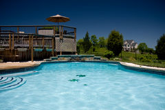 Water level view of pool and deck. View of a backyard swimming pool with a deck taken from the water level stock images