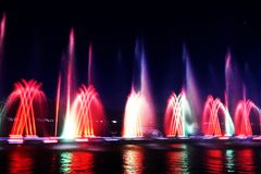 Water and light show. Beautiful colorful water and light show, blurry fountain background royalty free stock image