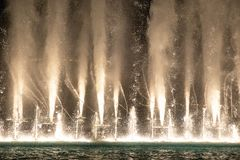 Water and light show of Dubai Mall fountains. Water and light show of the Dubai Mall fountains on a late evening. Dubai, UAE stock photography