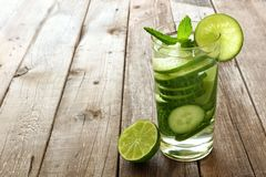 Water with lime and cucumber against wood Stock Image