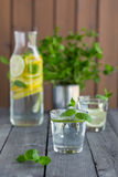 Water with lime and mint in glasses. On a old wooden table Royalty Free Stock Photography