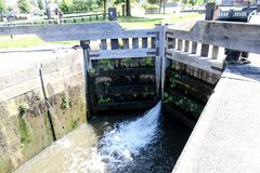 Water in the Lock in Wigan. The water spurts through the large wooden doors of the lock on the canal Stock Photography