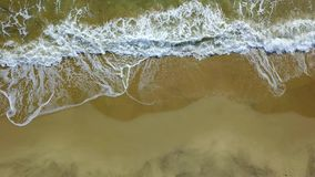 Water made by the waves comes ashore and goes to sea again. Aerial survey. Water made by the waves comes on the golden sandy ashore and goes to sea again. Aerial stock footage