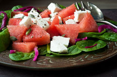 Water melon salad. Healthy salad of fresh water melon, spinach leaves, feta cheese and pickled cabbage. Served on a rustic plate on a slate stone table Stock Photography