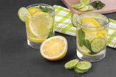 Water met citroen en komkommer en munt in een glaskop naast de helft van een verse citroen en komkommerplakken op een zwarte acht Royalty-vrije Stock Foto's