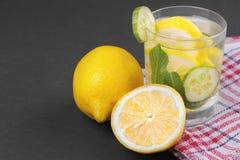 Water met citroen en komkommer en munt in een glaskop naast de helft van een verse citroen en komkommerplakken op een zwarte acht Royalty-vrije Stock Fotografie