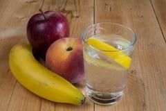 Water met citroen en vruchten Stock Fotografie