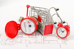 Water meter in shopping cart with alarm clock. Red water meter in shopping cart with alarm clock on draft background Royalty Free Stock Image