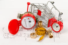 Water meter with shopping cart and pipe fittings. On draft background Stock Photos