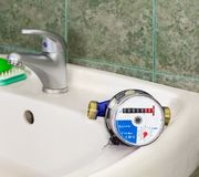 Water meter on the wash basin with handle mixer tap. Water meter on the wash basin on background of a handle mixer tap and wall with green tiles Royalty Free Stock Image