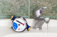 Water meter on the wash basin with handle mixer tap. Not connected meter for consumption measuring of a cold water on a wash basin beside mounted handle mixer Royalty Free Stock Photo