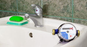 Water meter on the wash basin with handle mixer tap. Not connected residential water meter for consumption measuring of a cold water on a wash basin on Stock Photography