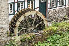 Water mill at the backside of a building. In Monschau in Germany. Editorial-All year round-Monschau-Germany; All year round, Monschau attracts many tourists stock image
