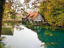 Water mill at Blautopf in autumn, Blaubeuren, Germany. The Blautopf (Blue Pot) is a fabled spring in Southern Germany and an entrance into an unique cave system Royalty Free Stock Image
